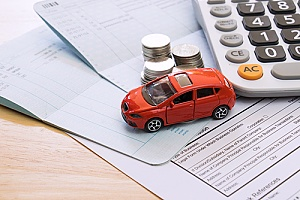 a model car on top of legal documents representing auto insurance