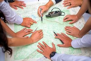 hands covering a map sales territory analyzed by a team
