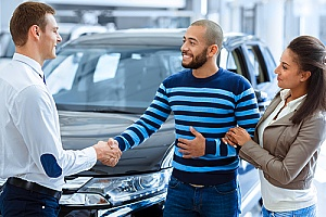 a couple shaking hands with a car dealer after a sale